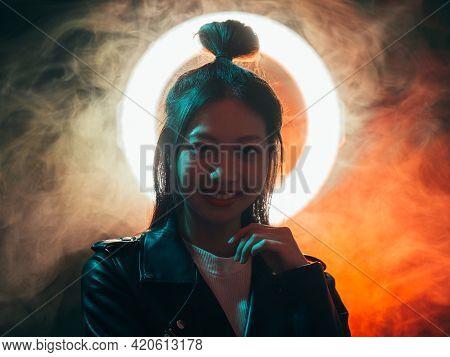 Cyberpunk Portrait. Future People. Grunge Style. Blue Neon Light Cheerful Asian Girl In Black Biker