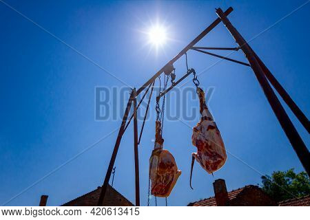 Shot From Below On Two Raw, Fresh Pork Hams Hooked On Hooks, Hanging On Metal Carrier. View On Sun R