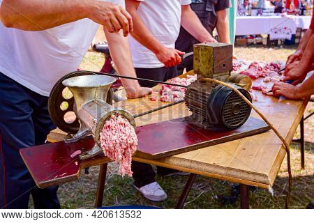 Men Are Working Together On Meat Grinder Machine, Forcemeat Process For Making Sausages.