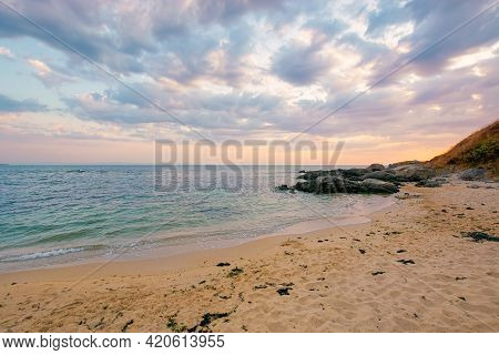 Summer Vacation Landscape By The Sea At Sunrise. Calm Water Washes Sandy Beach. Dramatic Clouds Abov