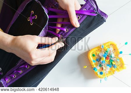 Cropped Shot Of Female Seamstress Or Tailor Using Scissors While Sewing Purple Corset With Lacing At