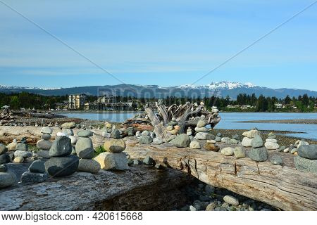 Parksville Bc ,canada. May 11th 2021.innukshuks On A Log With Mount  Arrowsmith And The Beach Club R