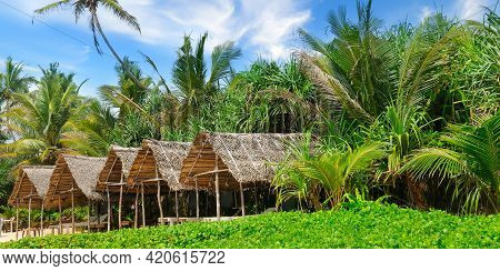 Beach Bungalows Set Against A Backdrop Of Lush Tropical Vegetation. The Concept Is Travel. Wide Phot