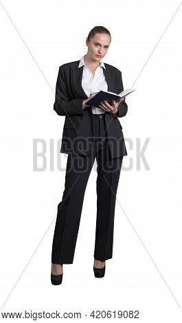 Attractive Business Woman In Formal Suit Is Holding A Planner, Notebook Or Her Notes And Looking Str