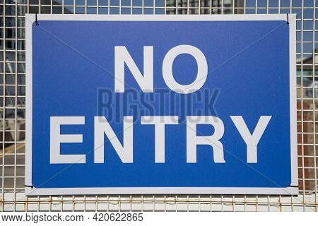 A Blue And White No Entry Sign On Some Fencing.