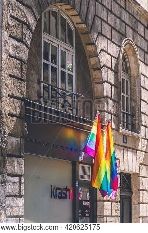 Lgbtq Flags Hanging Under Arch Windows Of Ancient Stone House During Paris Pride. Lgbtqia Culture Sy