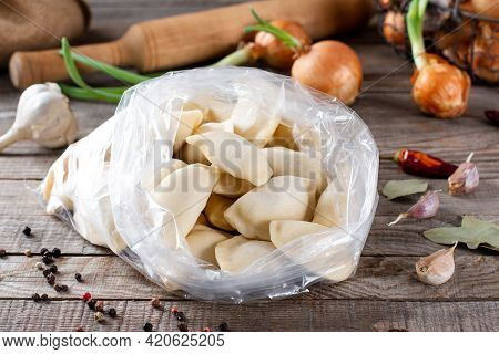 Dumplings. Frozen Dumplings In The Bag With Ingredients On A Wooden Table. Traditional Homemade Food