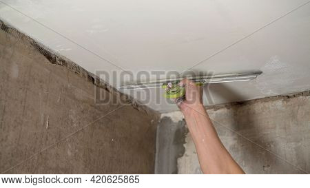 A Man Puts Putty On The Ceiling During Renovation Work. Hand With A Putty Knife And Putty, Apply The