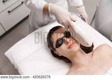 Beautician Eliminate Blemishes And Dark Spots On Female Client Skin. Cosmetologist Doing Elos Facial