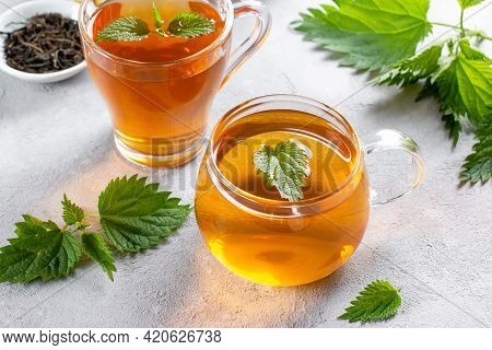 Nettle Tea In A Glass With Fresh Stinging Nettle Plant Inside, On The Table. Folk Remedy. The Source