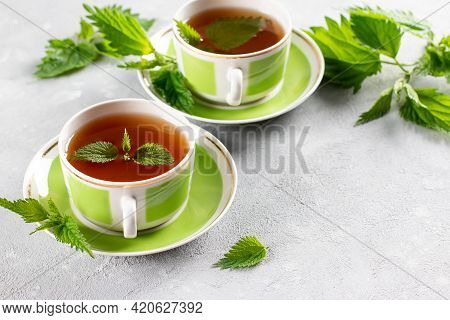 Nettle Tea In Two Cups, Fresh Stinging Nettle Herbs. Folk Remedy. The Source Of Vitamins. Copy Space