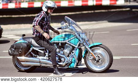Warsaw, Poland. 10 May 2021. Man With Goatee Beard Wearing Jeans, Boots And Helmet Is Idling On The