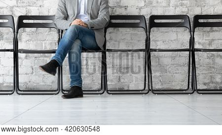 Single Job Candidate Waiting For Interview, Sitting Alone On Chair