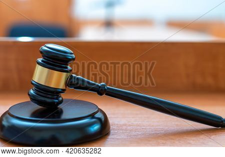 The Judge\'s Hammer Is Dark On A Light Table Against The Background Of The Courtroom