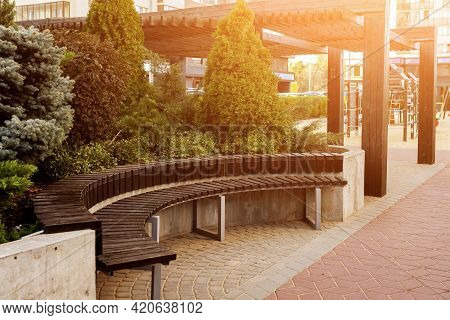 A Semi-circular Wooden Bench In A Small City Garden At Sunset. Pergola, Shrubs And Cypresses In The
