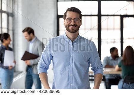 Portrait Of Happy Millennial Male Business Leader In Modern Office
