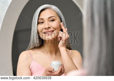 Mature Beautiful Happy Middle Aged Asian Woman, Older Grey Haired Lady Looking At Mirror Touching Fa