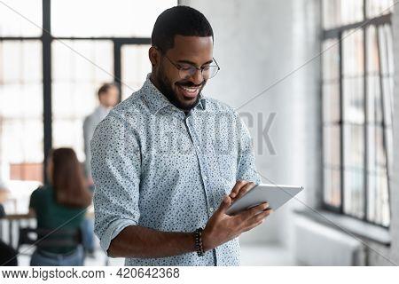 Happy Black Male Employee Reading On Digital Device Screen