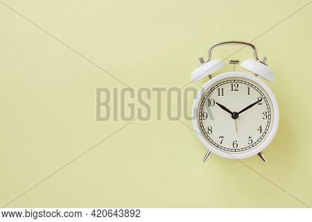White Alarm Clock On Pastel Yellow Minimalist Background On Right Frame
