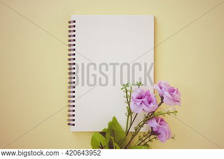 Spiral Notebook Or Spring Notebook In Unlined Type And Purple Flower On Pastel Yellow Minimalist Bac