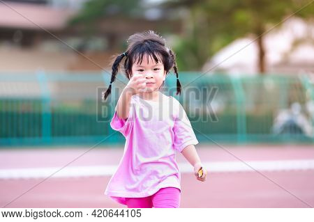Cute 4 Year Old Asian Girl Running And Having Fun. Happy Child Was Wearing A Pink Dress. Children Br