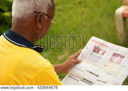 Focus On Shoulder, Shoulder Shot Of Old Man Busy Reading Morning News Paper - Concept Of Senior Peop