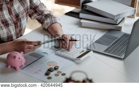 Woman Calculating Her Debt. Woman Hand Calculating Her Monthly Expenses During Tax Season With Coins