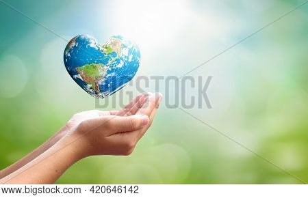 World Environment Day Concept: Man Opens Palms And Drags Heart Shaped Earth Globe Over Blurred Blue