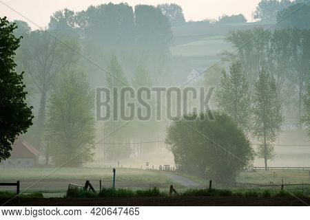 Beautiful Landscape In The Flemish Ardennes With A House Next To A Street And Fog In The Distance.
