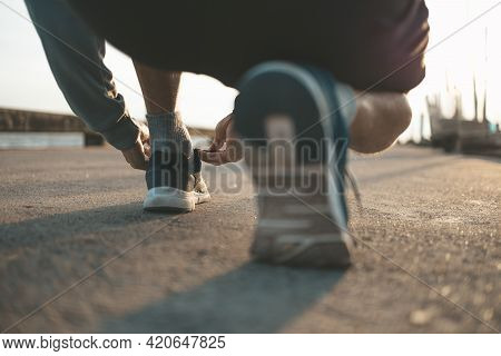 Closeup Of Man Tying Shoe Laces On The Road Before Running In Sunset. Sport And Workout Concept.