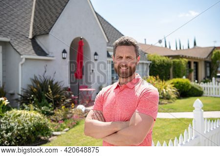 Smiling American Man With Arms Crossed Standing In Front Of His New Home. Buy, Sell, Real Estate, Pr