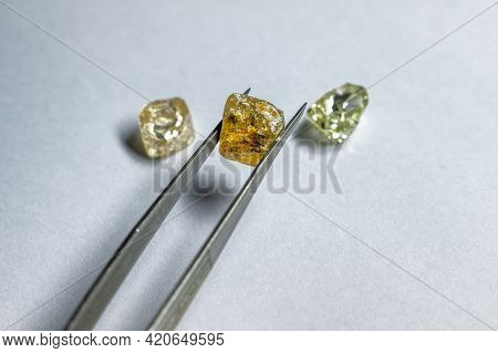The Colored Diamond Is Held In Place With Metal Tweezers. Two More Precious Stones Lie Nearby.