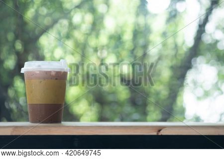 Iced Mocha Coffee In Small Size Glass On Wood Table Against Nature Background