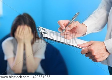 Doctor Writing About Depressed Woman During Psychotherapy Session. Sad Girl With Psychologist Conduc