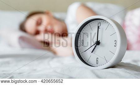 Happy Young Woman Sleeping Near Bed Side Alarm Clock. Calm Healthy Morning Sleep Of Woman In Pajamas