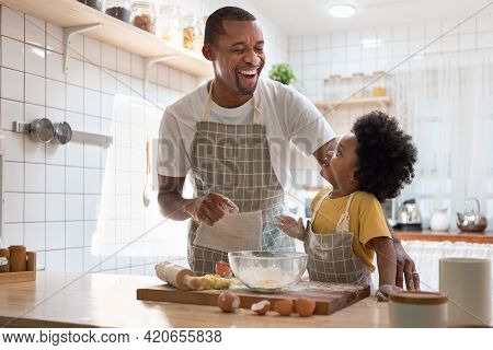 Happy African American Father And Little Son Smiling And Laughing While Cooking In Kitchen. Black Fa