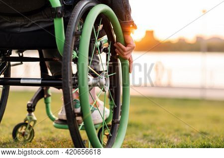 A Disabled Man Is Sitting In A Wheelchair. He Holds His Hands On The Wheel.