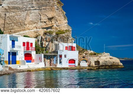 Scenic picturesque greek fishing village Klima with whitewashed traditional houses and colorful windows and doors on Milos island in Greece