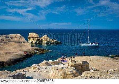 Yacht boat at famouse Sarakiniko beach white rocks tourist attraction with tourists on beach in Aegean sea on sunset, Milos island , Greece