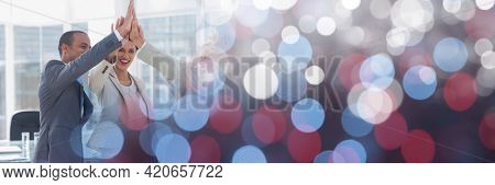 Composition of business people high fiving with spots of light. business, motivation and teamwork concept digitally generated image.