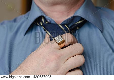 A Close-up Of A Hand Adjusting A Blue And Yellow Striped Tie Around His Neck. A Middle-aged Man With