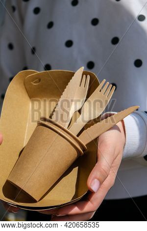 Female Hands Holding Wooden Forks And Paper Cups With Plates. Eco Friendly Disposable Tableware. Use