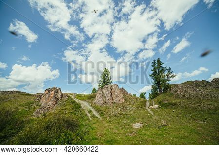 Scenic Alpine Landscape With Crossroads Of Two Dirt Roads On Hill By Rocks Under Blue Sky With Cloud