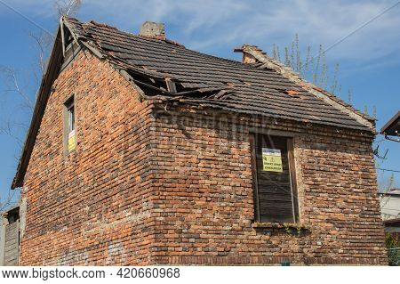 An Abandoned Abandoned Brick Empty House Against A Blue Sky And A Sign With The Inscription In Polis