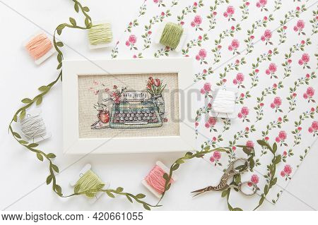Cross Stitch Typewriter Saying Hello Spring On Linen Canvas In White Frame, Floss Threads On Bobbins