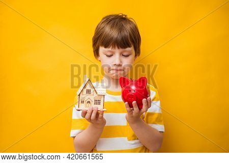 Childhood Dreams. Little Boy Holds His Dream House And Piggy Bank. Happy Life, House Or Mortgage Inv