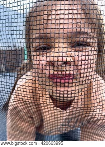 Little Girl Looks Into The Camera Through The Net.