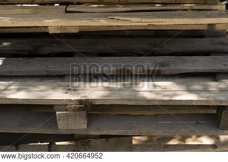 Old Wooden Pallets. Garbage Removal. Old Wooden Pallets For Recycling. Many Pallets Stacked In Stock