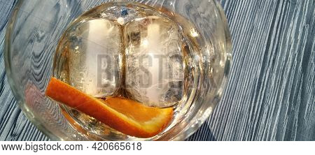Ice Cubes And Orange Slice Forming A Smiling Face At The Bottom Of An Almost Finished Drink - Looks