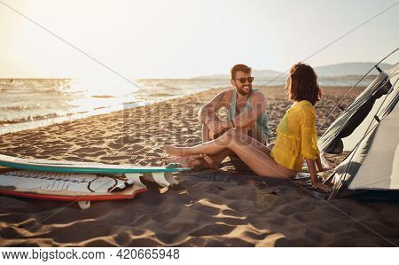 Young couple of surfers is sitting on sand and chatting while camping at the beach on a beautiful sunny day at sea. Summer, vacation, sea, relationship